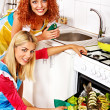 Stock Photo: Women prepare fish in oven.