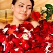 Young woman in rose petal — Stock Photo