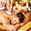 Man getting herbal ball massage treatments . — Stock Photo