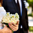 Bride and groom holding flower outdoor. — Stock Photo #40598141