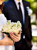 Bride and groom holding flower outdoor. — Stock Photo