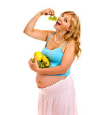 Pregnant woman eating vegetable. — Stock Photo