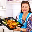 Mature woman preparing chicken at kitchen. — Stock Photo #42854259