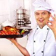 Man in chef hat cooking chicken — Stock Photo