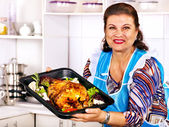 Mature woman preparing chicken at kitchen. — Stock Photo