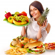 Woman choosing between fruit and hamburger. — Stock Photo #44263703