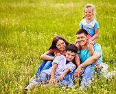Family on green grass. — Stock Photo