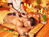 Man getting stone therapy massage . — Stock Photo