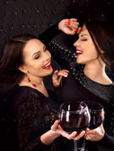 Twee sexy lesbische vrouwen met rode wijn. — Stockfoto