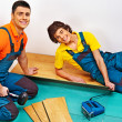 Repairmеn laying parquet at home — Stock Photo