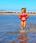 Child with beach ring running on  beach. — Stock Photo