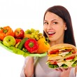 Woman choosing between fruit and hamburger. — Stock Photo