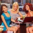 Women at laptop drinking cocktail in a cafe. — Stock Photo #48113181