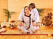 Male masseur doing massage woman in bamboo spa. — Stock Photo