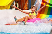 Child in bikini sliding water park. — Stock Photo