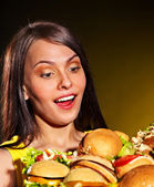 Thin woman holding hamburgers. — Stock Photo