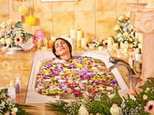 Woman taking a bath with flowers — Stock Photo
