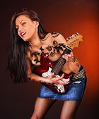 Aggressive girl with tattoo playing guitar. — Photo