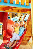 Children move out to slide in playground — Stockfoto