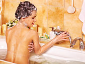 Woman using bath sponge in bathtub. — Stok fotoğraf