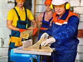 Builders Group with circular saw. — Stock Photo