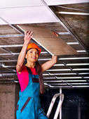 Woman installing suspended ceiling — Stockfoto