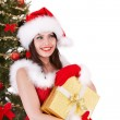 Christmas girl in santa hat and fir tree with gold gift box. — Stock Photo #6725286