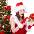 Christmas girl in santa hat and fir tree with red gift box. — Stock Photo #6725289
