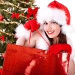 Christmas shopping of girl in santa hat, fir tree. — Stock Photo #6725300