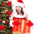 Christmas girl in santa hat and fir tree with red gift box. — Stock Photo #7893545