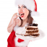 Girl in Santa hat eat cake . — Stock Photo #7893570