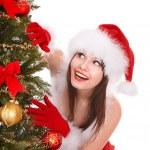 Girl in santa hat by christmas tree. — Stock Photo #7893572