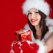 Girl in Santa hat holding gift box on red background. — Stock Photo #7893578