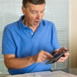 Senior man preparing USA tax form 1040 for 2012 - Stock Photo