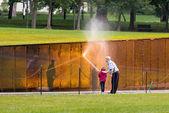 Man and girl washing wall at Vietnam memorial — Stock Photo