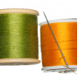 Orange and green bobbins of thread — Stock Photo