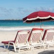Three beach loungers and umbrella on sand — Stockfoto