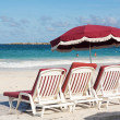 Royalty-Free Stock Photo: Three beach loungers and umbrella on sand