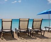 Three beach loungers and umbrella on sand — Stock Photo