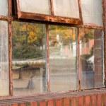 Old rusty window in warehouse reflecting fall — Stock Photo