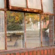 Old rusty window in warehouse reflecting fall — Stock Photo