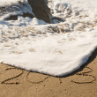 2013 in sand being covered by sea waves — Stockfoto