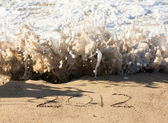2012 in sand being covered by sea waves — Stock Photo
