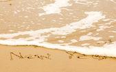 Happy new year written in sand on beach — Stock Photo