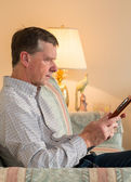 Старший мужчина, читая книгу на диване — Стоковое фото