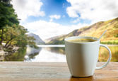 Cup of coffee on wooden table by lake — Stok fotoğraf