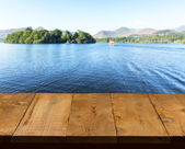 Old wooden table or walkway by lake — Stock Photo