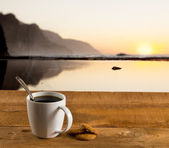 Cup of coffee on wooden table by ocean — Stock Photo