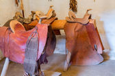Hand made saddles in spanish mission — Stock Photo