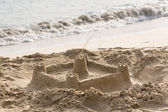 Childs sand castle on beach by ocean — Stock Photo
